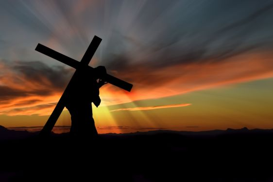 Christ carrying cross up Calvary on Good Friday over dark and stormy sky