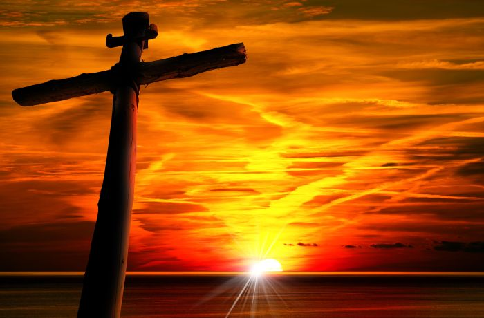 Cross silhouette at the beautiful sunset over the sea with cloudy sky.