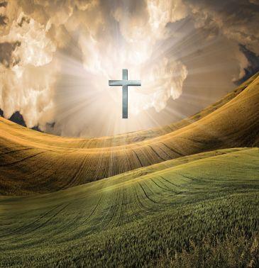Cross radiates light in sky over beautiful landscape